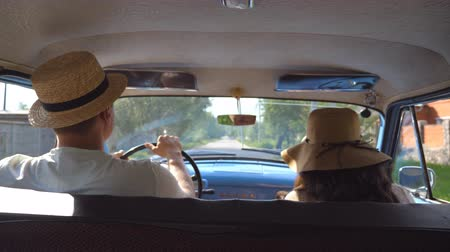 társ : Young couple in hats driving on country road in classic vintage car. Unrecognizable pair riding into old auto. Man and woman sitting at the front seat of a retro automobile. Trip concept. Slow motion