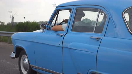 menekülés : Side view of unrecognizable man in hats driving at blue retro car after rain during summer travel. Young guy moving at his old vintage vehicle on highway. Slow motion Close up