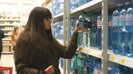 потреблять : Beautiful woman choosing bottle of mineral water at the supermarket. Young girl taking product from shelves at grocery section of shop. Slow motion Close up Стоковые видеозаписи