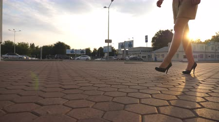 emancipation : Female legs in high heels shoes walking in the urban street. Feet of young business woman in high-heeled footwear going in city. Girl stepping to work. Sun flare at background. Slow motion Close up