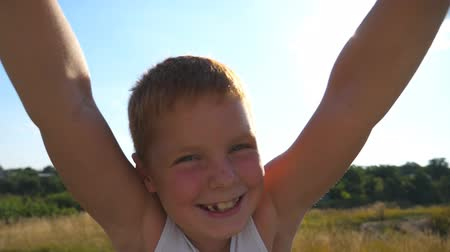 movimentar se : Father spinning his happy son in a meadow on a sunny day. Dad rotate smiling boy around at nature. Close up emotions of red hair child with glad expression on face. Slow motion