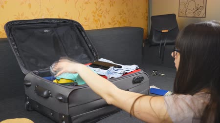 pasaport : Woman packing suitcase with personal stuff for trip on the couch in her room. Lady gets ready for flight to resort.Girl putting summer things in a bag. Concept of travel.Side view. Close up Stok Video