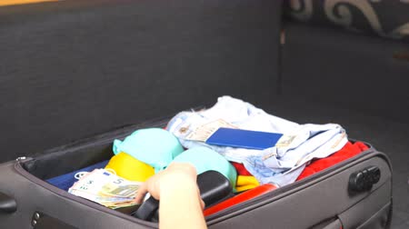 caso : Arms of young woman open a suitcase and unpack personal stuff. Arrival from the resort. Female hands lay out summer things from a bag. Concept of travel. Side view Close up