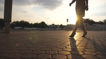 emancipation : Female legs in high heels shoes walking in the urban street at sunset. Feet of young business woman in high-heeled footwear going in the city with sun flare at background. Girl stepping. Slow motion Stock Footage