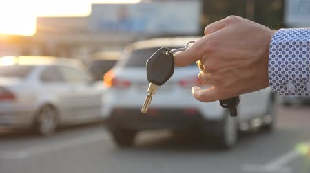 auto parking : Young business man walking at parking outdoor and holding at hand key of car. Arm of businessman with vehicle key. Guy going between rows of parking to his automobile. Close up Slow motion