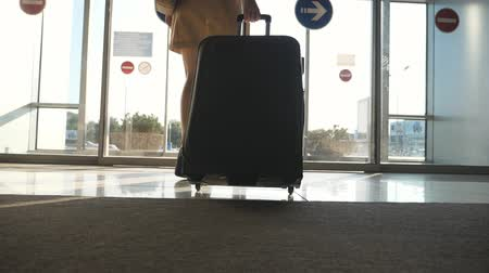 concourse : Woman in heels goes to exit from airport and roll suitcase on wheels. Girl walking with her suitcase along airport hall or waiting room. Business lady going with her luggage. Travel concept Slowmotion