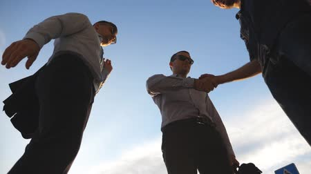 metáfora : Three businessmen farewell with each other each other and farewell and diverge in different directions. Colleagues shake hands with blue sky at city background. Business handshake outdoor. Slow motion