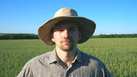 Portrait of confident farmer in hat looking into the camera against the background of green wheat field. Close up of young man in shirt standing in the meadow on sunny summer day