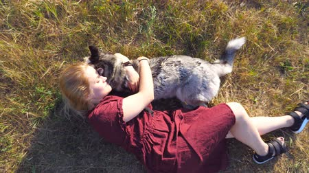 Beautiful woman with blonde hair lying on grass at meadow and hugging her husky dog. Young girl spending time together with her pet at field. Love and friendship with domestic animal. Top view
