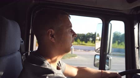 Profile of male truck driver. Trucker riding at the car. Man holds hand on the steering wheeland driving truck through countryside on a warm summer day. Side view Close up