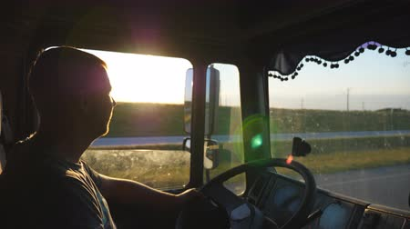Man driving a truck and carefully watching the road. Caucasian guy is riding through the countryside on the sunset background. Profile of lorry driver inside the cab. Side view Slow motion Close up Stock mozgókép