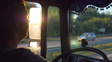 Man driving truck and carefully watching the road. Caucasian guy is riding through countryside with beautiful landscape at background. Profile of lorry driver inside the cab. Slow motion Close up Stock mozgókép