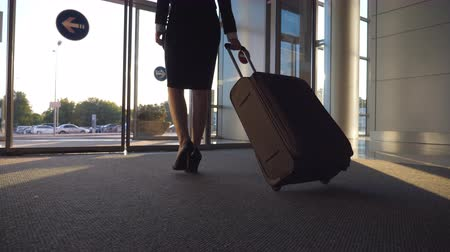 concourse : Business lady going from airport with her luggage. Woman in heels walking with her suitcase from terminal to city street. Girl stepping and rolling bag on wheels. Trip concept. Slow motion Close up