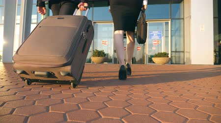 valigetta : Business man and woman going to the airport with their luggage. Young businessman carrying suitcase on wheels and walking with his female colleague to terminal hall. Trip or travel concept Slow motion