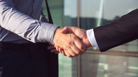 pozdravit : Dolly shot of two businessmen shaking hands after successful deal near office building. Close up of young colleagues congratulating each other in urban environment. Handshake of business partners Dostupné videozáznamy