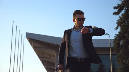 hurry up : Young businessman in a formal black suit looking at his watch and quickly going with his luggage. Handsome man in sunglasses being late for the meeting or work after flight. Close up Low angle view