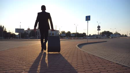 hurry up : Rear view of unrecognizable businessman walking on city street and pulling suitcase on wheels at sunset. Young confident man in a black suit being late for the meeting or job after flight. Close up