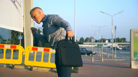 aktatáska : Close up of cheerful young businessman with briefcase funny dancing while walking near airport terminal at sunset. Happy handsome man in shirt with bag celebrating his achievement and success