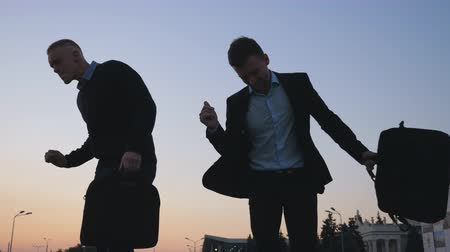 aktatáska : Close up of two happy young businessmen with briefcases funny dancing while walking after successful business deal at city street. Cheerful colleagues celebrating achievement at sunset. Low angle view Stock mozgókép