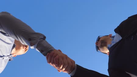 pozdravit : Low angle view of two successful businessmen meeting and shaking hands on the clear blue sky background. Young confident colleagues greeting each other outdoor. Business handshake outside. Slow motion