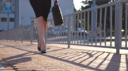 emancipation : Female legs in high heels shoes walking in the urban street at sunny day. Feet of young business woman in high heeled footwear. Girl with bag goes to work. Slow motion Close up Stock Footage
