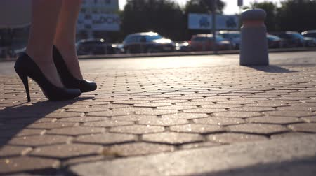 emancipation : Female legs in high heels shoes walking in the urban street near auto parking. Business woman stepping to work. Young girl on his way to office. Side view Slow motion Close up