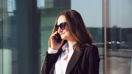 jó hangulatban : Portrait of young smiling businesswoman talking on phone. Happy beautiful woman speaking on smartphone near modern business center. Business girl is in a good mood. Slow motion Close up