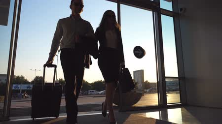 concourse : Businessman with his female colleague walking through enter to terminal and roll suitcase on wheels. Business man and woman stepping to the airport or office building together. Slow motion Close up