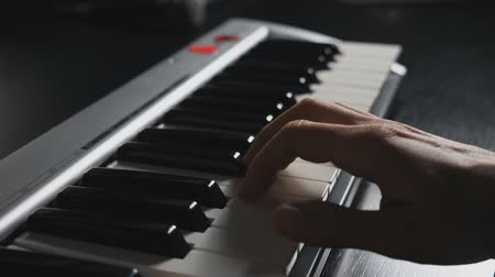 synth : Fingers of pianist pressing at synthesizer keys. Hands of man playing solo of music at piano. Slow motion Top view Close up Stock Footage