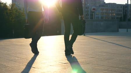 unrecognizable people : Two businessmen with briefcases walking in city street with sun flare at background. Business men commute to work together. Confident guys being on his way to office. Colleagues going outdoor. Slow mo