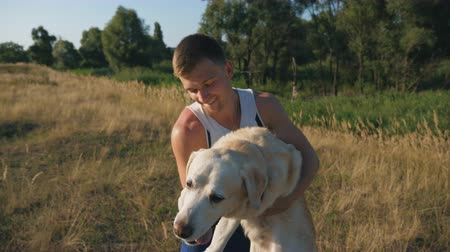 társ : Young man holds labrador in his arms. Guy spends time together with his pet in nature. Love and friendship to domestic animal. Beautiful landscape at background. Front view Slow motion Close up