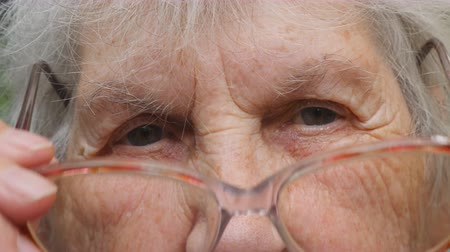 меланхолия : Old woman puts on glasses and looking at camera. Granny wearing eyeglasses outside. Portrait of sad grandmother outdoor. Close up Slow motion Стоковые видеозаписи