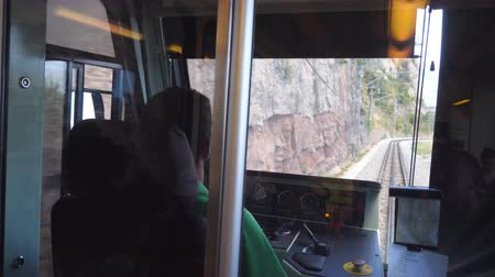 machinist : Unrecognizable train driver drives electrical train among mountain road. Point of view from driver cabin to railway tracks. Rear back view POV Slow motion Close up Stock Footage