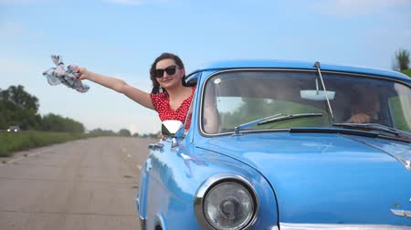 Young girl with scarf in hand leaning out of window of vintage car and enjoying ride. Woman looks out from moving retro auto with beautiful landscape at background. Slow motion Close up Stock Footage