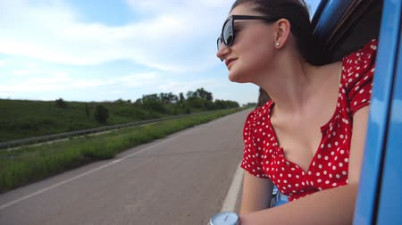 Profile of young girl in sunglasses leaning out of vintage car window and enjoying trip. Woman looks out from moving vintage auto. Travel concept. Attractive lady in old vehicle. Slow motion Close up Stock Footage