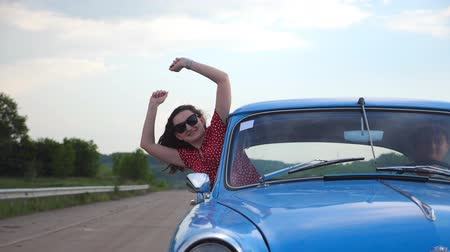 Young couple traveling on vintage car at country road in summer time. Attractive woman leaning out from window of moving retro auto and enjoying trip. Travel and freedom concept. Slow motion Close up