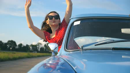 Young girl in sunglasses leaning out of vintage car window and enjoying trip. Woman looks out from moving retro auto. Travel and freedom concept. Blurred background. Front view Slow motion Стоковые видеозаписи