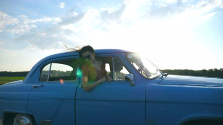 Attractive girl in sunglasses leaning out of vintage car window and enjoying trip. Young couple travel on retro car in summer time. Travel concept. Sun shining at background. Slow motion Close up