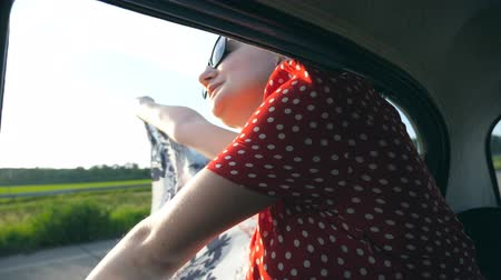 Young attractive girl in sunglasses with scarf in her hands leaning out of window vintage car and enjoying ride in summer time. Travel and freedom concept. Inside view Slow motion Close up Stock mozgókép