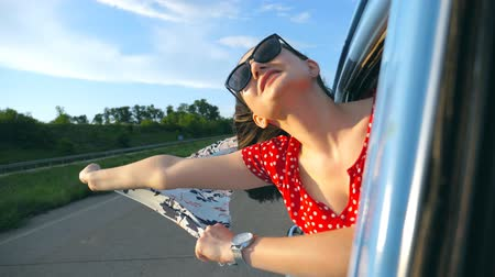 Young girl in sunglasses with scarf in her hands leaning out of window retro car and rejoicing travel. Attractive woman smiles and enjoys trip in sunny day. Travel concept. Slow motion Close up Stock mozgókép