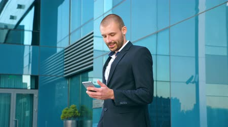 Young businessman using smart phone near office and celebrating achievement. Business man read good news on smartphone and having positive emotions. Portrait of guy is happy with success. Slow motion