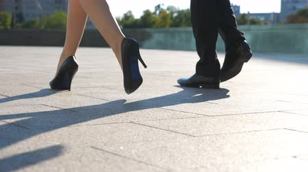Feet of business man and woman in high heels shoes walking in urban street. Businessman and businesswoman commute to work together. Legs stepping to job. Colleagues going outdoor. Slow motion Close up Stockvideo