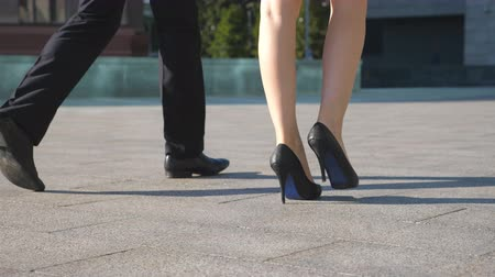 Feet of business man and woman in high heels shoes walking in urban street. Businessman and businesswoman commute to work together. Legs stepping to job. Colleagues going outdoor. Slow motion Close up Стоковые видеозаписи