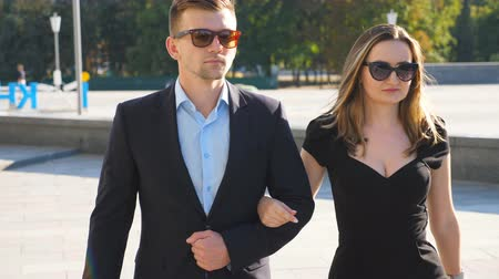 Young couple of male and female business people walking in the city street. Portrait of businessman and businesswoman going outdoor with urban landscape at background. Close up Slow motion