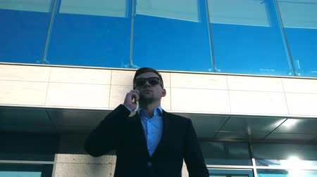 banqueiro : Portrait of young businessman in sunglasses talking on phone outdoor near office. Close up of handsome business man speaking on cellphone with modern business building at background. Slow motion