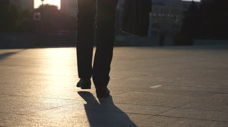 aktatáska : Feet of young businessman with a briefcase walking in city street. Business man commuting to work. Confident guy in suit being on his way to work. Cityscape backround. Slow motion Rear view Close up Stock mozgókép