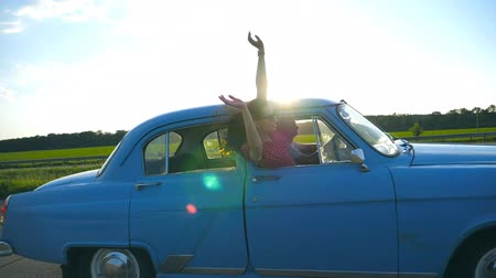 Attractive girl in sunglasses leaning out of vintage car window and enjoying trip. Young couple travel on retro car in summer. Travel concept. Sun shining at background. Slow motion Close up