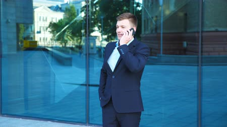 Handsome businessman talking on phone near office and celebrating achievement. Young business man heard good news on cellphone and having positive emotions. Portrait of guy is happy with success