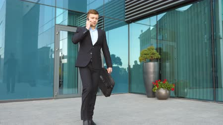 Young businessman talking on phone and walking in city street. Handsome man commuting to work and speaking on cellphone outside. Confident guy in suit having business conversation outdoor. Slow motion Stock Footage