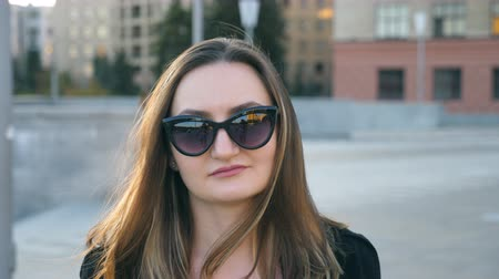 Portrait of young businesswoman in sunglasses walking in city street. Attractive business woman looking at the camera. Face of confident girl commuting to work. Close up Slow motion